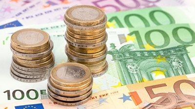 Geldscheine und Münzstapel